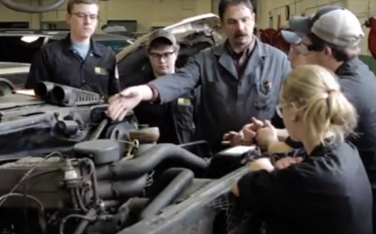Teacher showing students an engine