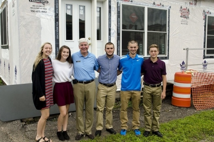 Governor Snyder standing with 5 students outside building under construction