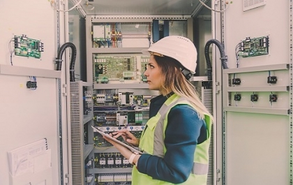 Woman electrician in power distribution house