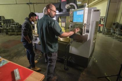 Machining instructor showing student equipment