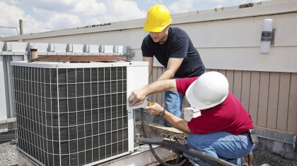 Workers working on roof top climate control unit