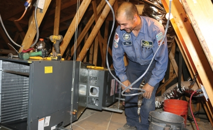 Climate control worker in attic working on units